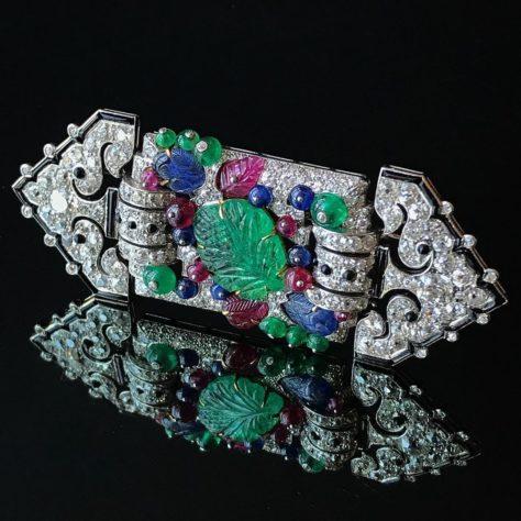 UNE BROCHE ART DÉCO MULTI-GEMME ET DIAMANT 'TUTTI FRUTTI', CARTIER Émeraudes sculptées, perles émeraude, rubis et saphir, plaques d'onyx, diamants taille ancienne, platine et or, 3 3/8 ins., Vers 1930, signées Cartier @ Christie's Maharajas & Mughal Magnificence New York, 19 juin 2019